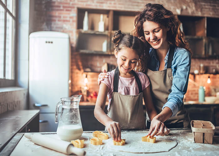 mom with girl baking cookies